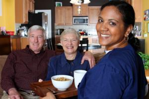 caregiver serving food to elderly couple
